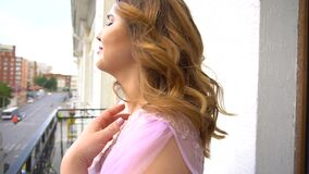 Pregnant woman on a balcony. Pregnant woman in pink peignoir on a balcony stock footage