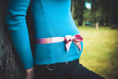 Pregnant woman with a pink ribbon. On her belly royalty free stock images