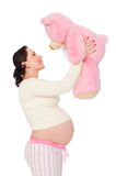 Pregnant woman with pink teddy bear Stock Image