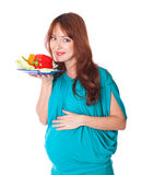 A pregnant woman with a plate of vegetables Stock Photo