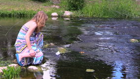 Pregnant woman play with paper ship on river water stock video