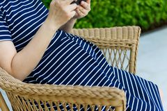 Pregnant woman play smartphone while sitting Royalty Free Stock Photos