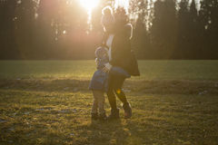 Pregnant woman playing with child outdoors Royalty Free Stock Photos