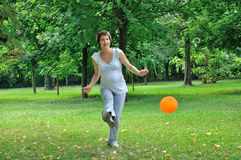 Pregnant woman playing football Royalty Free Stock Image