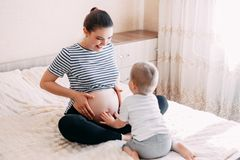 pregnant woman playing and hugging with her second baby royalty free stock photo