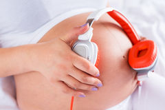 Pregnant woman playing music for the baby Stock Photo
