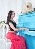 Pregnant woman plays on the piano. Stock Photos
