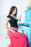 Pregnant woman plays on the piano. Royalty Free Stock Photos