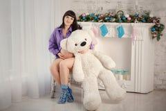 The pregnant woman with a polar teddy bear Royalty Free Stock Photography
