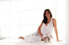 Pregnant woman portrait with bear toy Stock Image