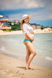 Pregnant woman posing on beach and holding hands on stomach Stock Photos