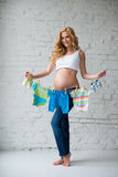 Pregnant woman posing with children`s clothes on a brick wall background. Royalty Free Stock Image
