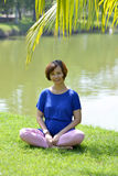 Pregnant woman posing in park with yoga style Royalty Free Stock Image