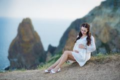 Pregnant woman posing sitting on cliff mountain wearing airy whit dress with blue sea on background stock image