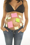 Pregnant woman with post its in her belly Royalty Free Stock Photos