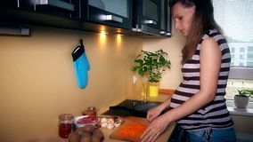 Pregnant woman pour sunflower oil into cooking pan and put shredder carrots stock video