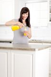 Pregnant Woman pouring Orange Juice Stock Images