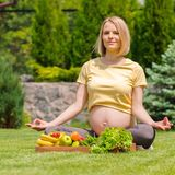 Pregnant woman practicing meditation and relaxation in nature Stock Photo
