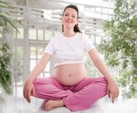 Pregnant woman practicing yoga stock images