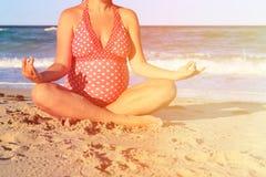 Pregnant woman practicing yoga at beach Royalty Free Stock Photos