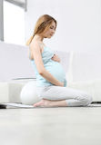 Pregnant woman practicing yoga Stock Image