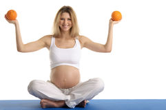 Pregnant woman practicing yoga with oranges