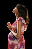 Pregnant Woman Praying. Portrait of African American woman praying isolated over black background Stock Photography