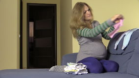 Pregnant woman prepare baby newborn clothes on sofa at home stock video