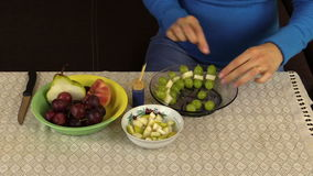 Pregnant woman prepare dessert from grapes and fruit pieces stock footage