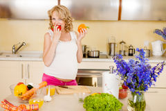 Pregnant woman prepares vegetable salad. At home royalty free stock photo