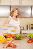 Pregnant woman prepares vegetable salad. At home royalty free stock photography