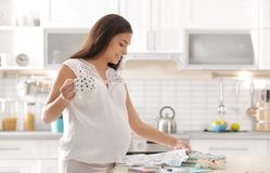 Pregnant woman preparing baby clothes for maternity hospital. In kitchen stock images