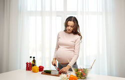 Pregnant woman preparing food at home Royalty Free Stock Image