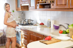 Pregnant woman preparing food in the kitchen Royalty Free Stock Photo