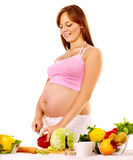 Pregnant woman preparing food . Stock Image