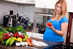 Pregnant woman preparing a healthy meal in the kitchen Royalty Free Stock Photography