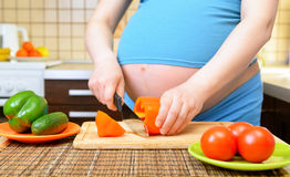 Pregnant woman preparing a healthy meal in the kitchen Stock Photo