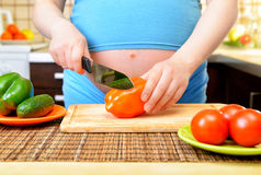 Pregnant woman preparing a healthy meal in the kitchen Stock Photography