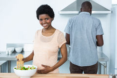 Pregnant woman preparing salad in kitchen Stock Photography
