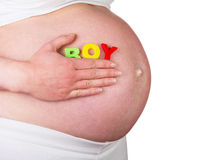 Pregnant woman presses hand to her stomach word BOY isolated. Stock Image