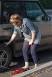 Pregnant woman pumping up wheel Royalty Free Stock Photo