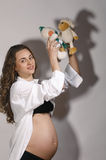 Pregnant woman with puppet Stock Images