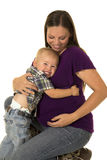 Pregnant woman in purple shirt arms around her young boy Royalty Free Stock Image