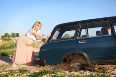 Pregnant woman pushing car Royalty Free Stock Photos