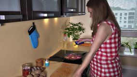 Pregnant woman put spice on baking meal in cooking pan. Static shot. 4k UHD stock video