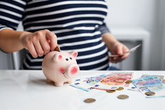 Pregnant woman putting coin into piggy bank Stock Photography