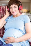 Pregnant woman putting headphones over bump Royalty Free Stock Images