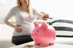 Pregnant woman putting money in piggy bank Royalty Free Stock Images