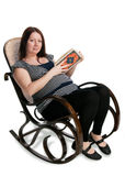 Pregnant woman reading a book Stock Images