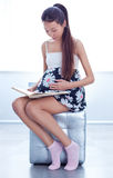 Pregnant woman reading book Stock Image
